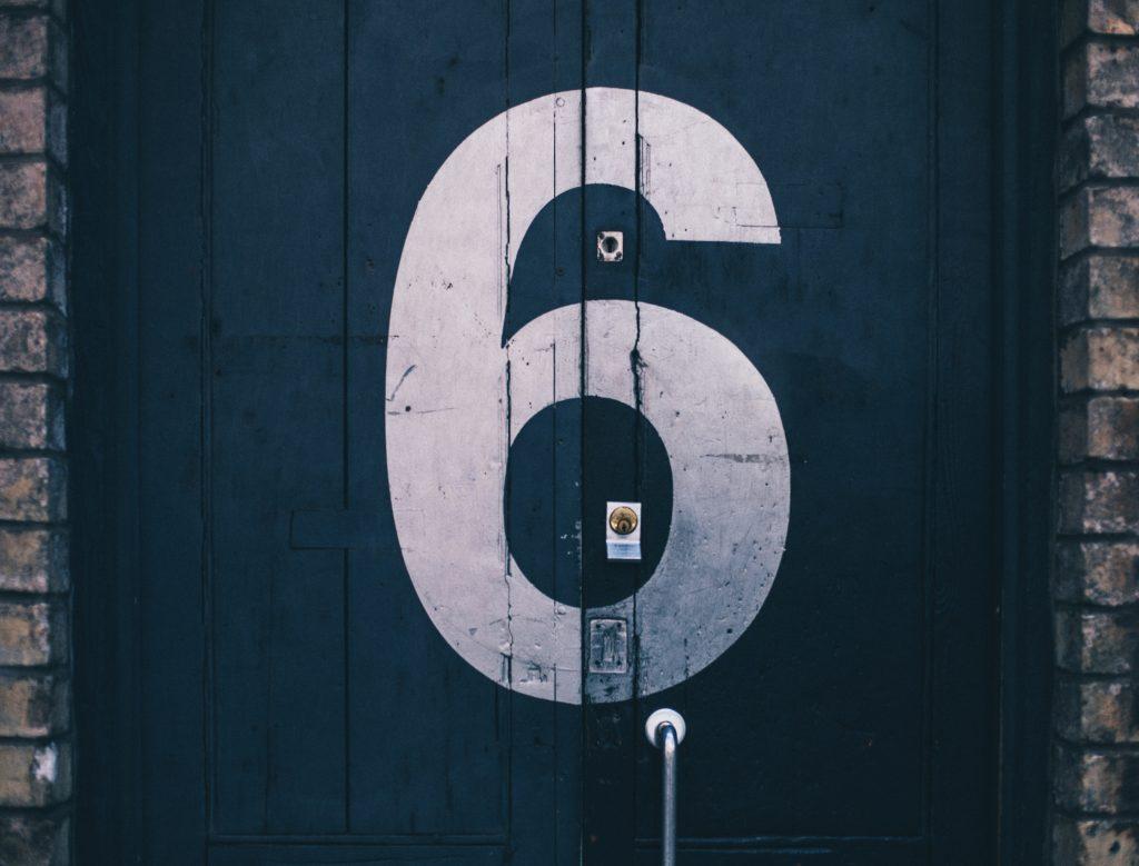 Chiffre six sur une porte en bois foncée